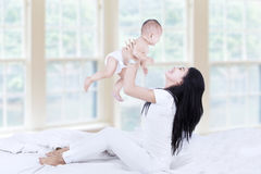 Mom playing with baby. Side view of young asian mom lifting happy baby into air above head Stock Images