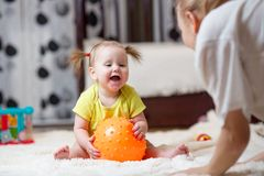 Mom playing ball with baby indoor Royalty Free Stock Images