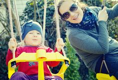 Mom playing with her daughter on a swing in the park. Royalty Free Stock Image