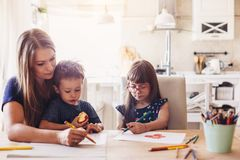 Mom drawing with her children. Mom playing with her 2 years old son and preschool daughter at home. Mother drawing with pencils together with children stock photos