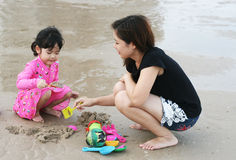 Mom is playing with kid on the beach Royalty Free Stock Photo