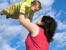 Mom is playing with son. A woman is playing with her son in the skies royalty free stock photography