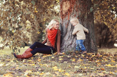 Mom playing with son child in autumn park. Under tree Stock Images