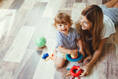 Mom playing with son on a floor Royalty Free Stock Image