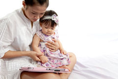 Mom is playing tablet with her baby Stock Photography
