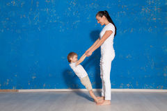 Mom playing with young son in a room. With blue walls Stock Image