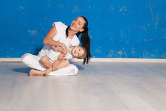 Mom playing with young son in a room. With blue walls Royalty Free Stock Photo