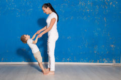 Mom playing with young son in a room. With blue walls Stock Photos