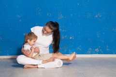 Mom playing with young son in a room. With blue walls Stock Photo