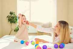 Mom plays with baby in the room indoors. Mom plays with the baby in the room indoors Royalty Free Stock Photos