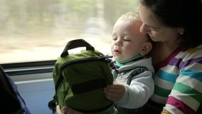 Mom plays with the baby son in a moving train near the window. The boy is on his mother`s lap. stock video footage