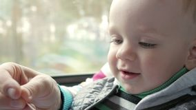 Mom plays with the baby son in a moving train near the window. The boy is on his mother`s lap. Mom plays with the baby son in a moving train near the window stock video
