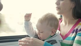 Mom plays with the baby son in a moving train near the window. The boy is on his mother`s lap. stock footage