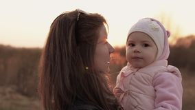 Mom plays with daughter and having fun against of sunset sky. Slow motion shot stock footage