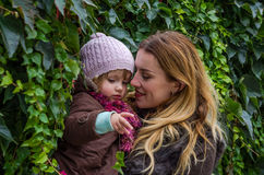 Mom plays with her daughter on a background of green vine leaves sunny autumn day Stock Photos