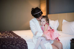 Mom plays with her daughter on bed and hugging Royalty Free Stock Images
