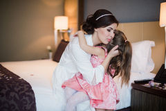Mom plays with her daughter on bed and hugging Royalty Free Stock Photo