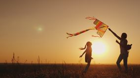 Mom plays with her daughter. Carelessly launch a kite. Happy life, summer activity concept royalty free stock photography