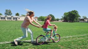 Mom plays with her daughter, teaching her to ride a bicycle stock video footage