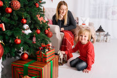 Mom plays with her son near Christmas tree Royalty Free Stock Images
