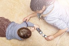 Mom, play, son, kid, happy, fun, family, toy cars, at home, on t. Mom plays with his son in typewriters at home on the carpet Royalty Free Stock Image
