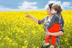Mom pointing to rapeseed field. Mother holding son and poiting something to him in rapeseed field royalty free stock image