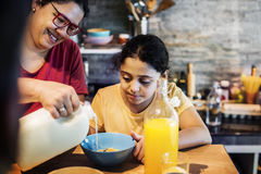 Mom pouring milk to daughter cereal bowl Stock Image