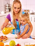 Mom pours juice  at kitchen. Stock Photography