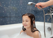 Mom pours a little girl out of the shower Royalty Free Stock Image