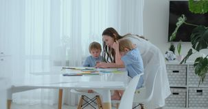 Mom praises two sons for their drawings. Family support and childcare, motherhood.  stock video