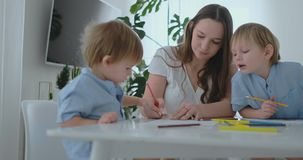 Mom praises two sons for their drawings. Family support and childcare, motherhood.  stock footage