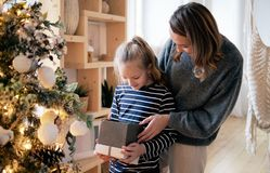 Mom present her daughter Christmas gift. Sunny Christmas morning. Natural soft colors stock images