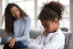 Mom or psychologist tries to talk to upset african girl. Mom or psychologist talking counseling upset offended african american child girl feels sad insulted royalty free stock image