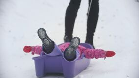 Mom pulling a sled in which lying her funny daughter stock footage
