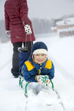 Mom pulls a sled with his son on snowy road Stock Photo