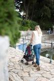 Mom pushing baby stroller Stock Photos