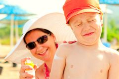 Mom puts on the babys skin lotion for sun protection Royalty Free Stock Image