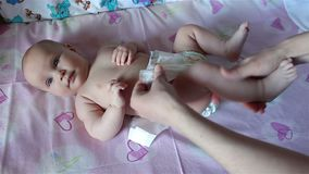 Mom puts a diaper on the baby