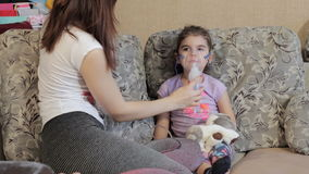 Mom puts little daughter inhalation mask. Begin making inhalation. stock video