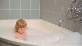 Mom puts the little girl in the bath stock video footage