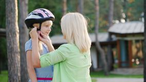 Mom puts on a protective helmet for her daughter. Concept - care and safety stock video