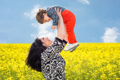 Mom raise uop her son in canola field Royalty Free Stock Images