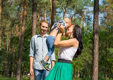 Mom raised up her son and laughs. Dad stands next to her and smiles. Happy family is resting in the park stock photo