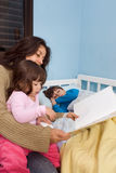 Mom Reading Bedtime Stories. Mother reading her children bedtime stories. Her daughter is sitting on her lap and her son is lying in bed stock photo