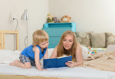 Mom reading a book son. Woman shows a child reading a book lying on the bed Royalty Free Stock Photo