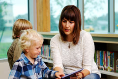 Mom reading book to children. Mom and children at library reading books Royalty Free Stock Photography