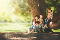 Mom reading a book to her children. Mother and daughters sitting under the tree on summer lawn. Happy family playing outdoors. Pretty young mom reading a book to Royalty Free Stock Image