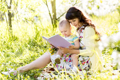 Mom reading a book to kid outdoors Stock Images