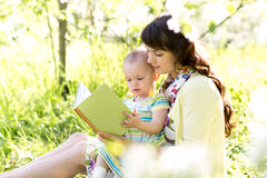 Mom reading a book to kid outdoors Royalty Free Stock Photography