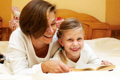 Mom reading a book to little daughter Stock Images